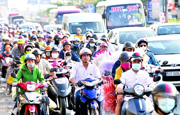 People from the Mekong Delta streaming back to HCMC in National Highway 1A, Binh Chanh district on February 20 (Photo: SGGP)