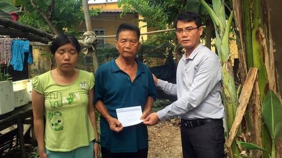 Đại diện Báo SGGP trao tiền hỗ trợ gia đình chị Nhất, anh Sinh