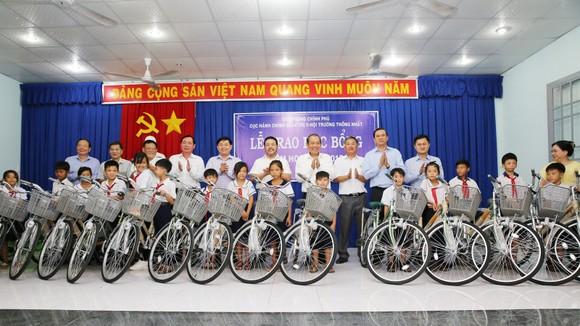 Phó Thủ tướng Thường trực Chính phủ Trương Hòa Bình cùng đại diện các tổ chức, đơn vị trao 100 chiếc xe đạp cho các em học sinh. Ảnh: VGP
