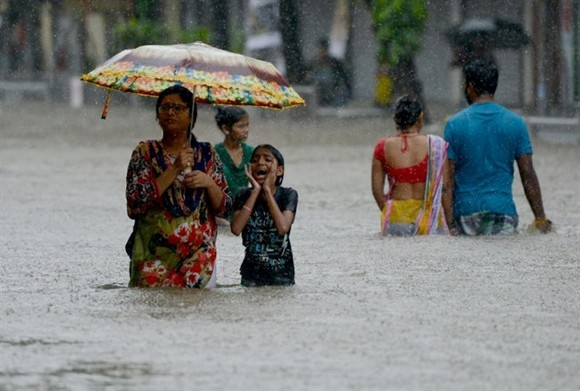Days of intense monsoon downpours have deluged the densely-populated city of more than 20 million, paralysing crucial local train services and leaving commuters to wade through swirling waist-high waters. Photo AFP/VNS