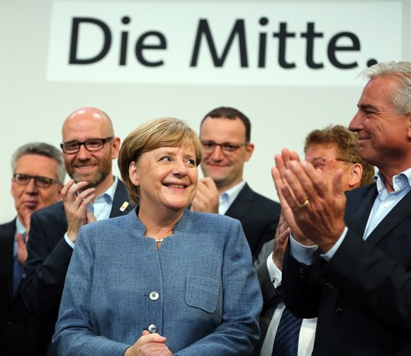 German sitting Chancellor Angela Merkel (L, Front) is applauded after the preliminary exit poll at the Christian Democratic Union (CDU) party's headquarters in Berlin, Germany, on Sunday
