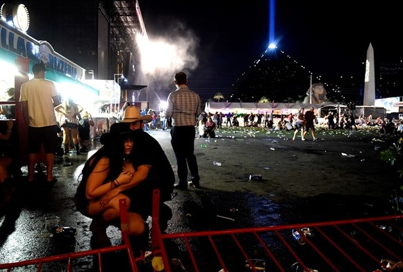 People take cover at the Route 91 Harvest country music festival after apparent gun fire was heard on October 1 in Las Vegas, Nevada.  AFP/VNS Photo
