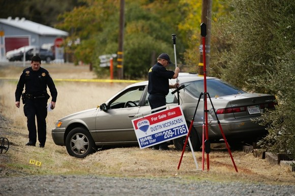 Law enforcement officers examine a vehicle that was involved in a shooting Tuesday, in Rancho Tehama, California. Four people were killed and nearly a dozen were wounded, including several children, when a gunman went on a rampage at multiple locations, i