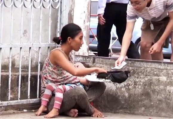 Photo captured from a clip showing a woman holding a sleeping girl in her arms begs for money at the gate of the Children's Hospital No 2 in District 1, HCM City. — Video clip nguoitieudung.com.vn