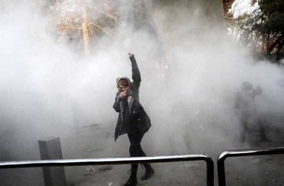 A woman raises her fist amid tear gas at the University of Tehran during a protest on December 30, 2017. – AFP/VNA Photo