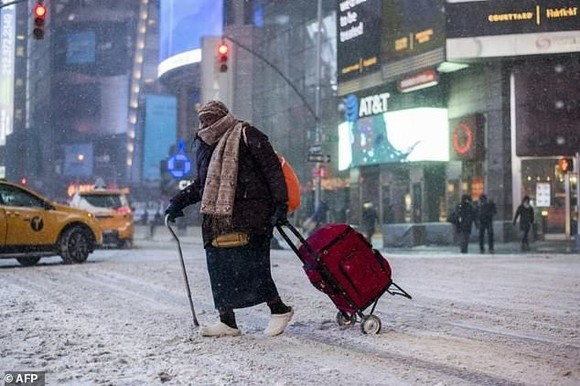 An elderly woman makes her way through New York's Times Square as snow pelts the Big Apple. — AFP Photo