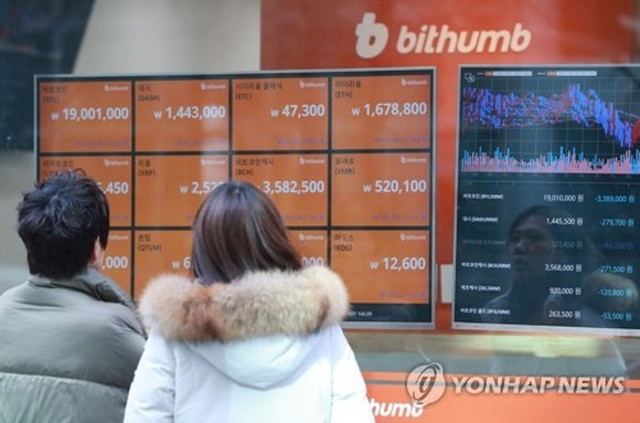 Two people read tables displayed at Bithumb, the largest cryptocurrency exchange in South Korea, in central Seoul on Jan. 11, 2018. (Yonhap)