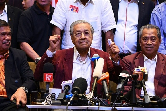 Former Malaysian Prime minister and opposition candidate Mahathir Mohamad celebrates with other leaders of his coalition during a press conference in Kuala Lumpur on early Thursday. — AFP/VNA Photo