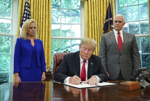 US President Donald Trump -- flanked by Homeland Security Secretary Kirstjen Nielsen (left) and Vice President Mike Pence -- signs an executive order to end family separations at the border.—AFP/VNA Photo
