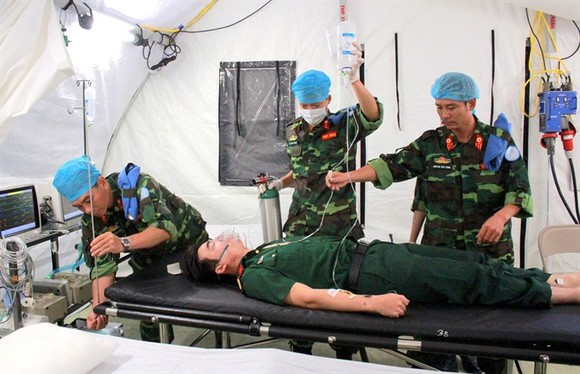 Vietnamese medical officers of the field hospital to be deployed in South Sudan are carrying out mock examination and treatment of injured patient. — VNA/VNS Photo Xuân Khu