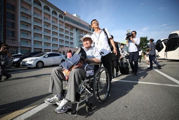 This photo taken by Joint Press Corps shows an elderly South Korean man in a wheelchair supported by his family moving to board a bus bound for a Mount Kumgang resort on North Korea's east coast, the venue for his long-awaited family reunion event. (Yonha