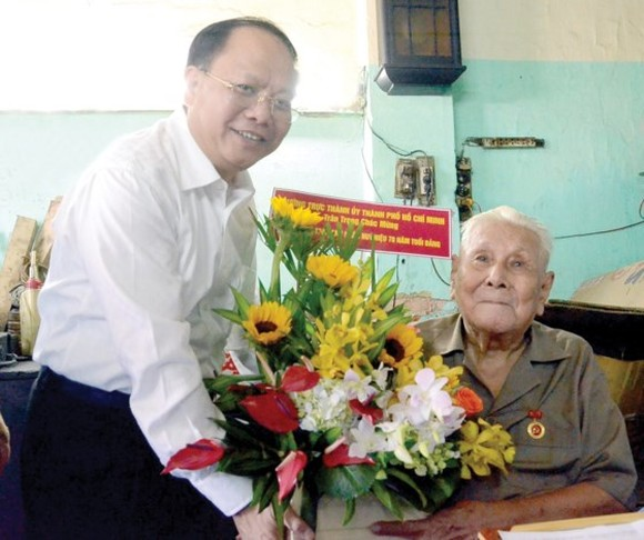Deputy Standing Secretary of the Ho Chi Minh City Party Committee Tat Thanh Cang presents the 70-year Party membership badge to Party member Ly Toan Anh. (Photo: Sggp)