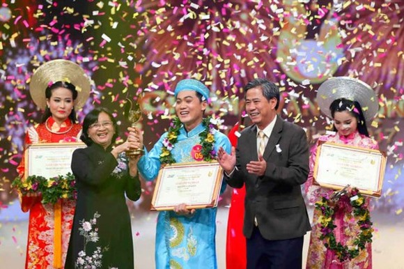Than Thi Thu ( in black Ao Dai), head of the Ho Chi Minh City Party Committee's Commission for Propaganda and Education, hands over the Golden Bell to Nguyen Van Khoi. (Photo: Sggp)