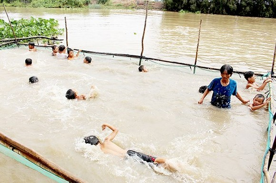 Mrs. Tran Thi Kim Thia is coaching kids in swimming.