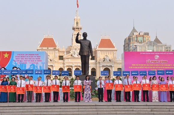 Chairman and Vice chairwoman of the municipal People's Committee, Nguyen Thanh Phong and Nguyen Thi Thu hand over emulation flags to representatives of departments and units. (Photo: Sggp)