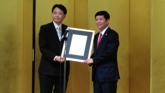 Vietnamese Ambassador to Japan Nguyen Quoc Cuong (R) hands over the Decision appointing Japanese doctor Nagato Natsume  Honorary Consul of Vietnam in Aichi. (Photo: Sggp)