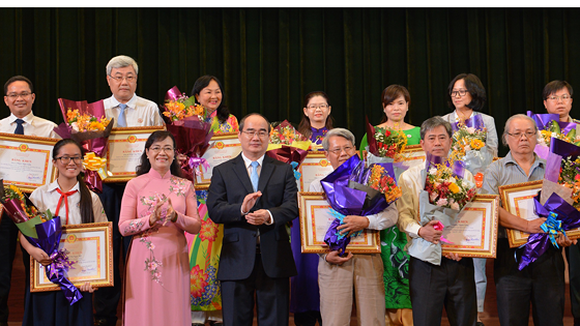 Secretary of HCM City Party Committee Nguyen Thien Nhan presents certificates of merit to honored individuals and units.  (Photo: Sggp)