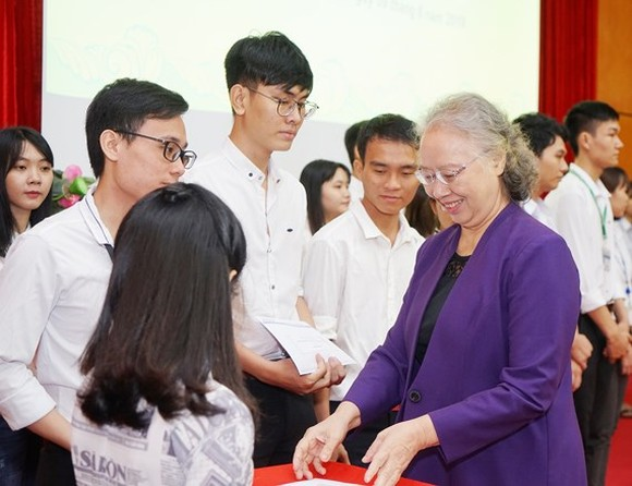 Chairperson of the Nguyen Van Huong scholarship fund council Dr. Truong Thi Xuan Lieu presents scholarships to students. (Photo: Sggp)