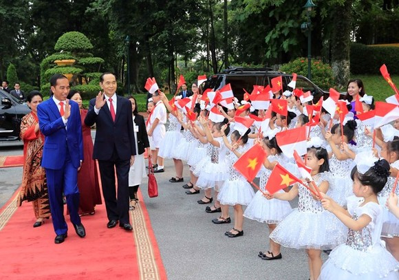 Indonesian President Joko Widodo (L) is welcomed by Vietnamese children at the official welcome ceremony for him and his spouse in Hanoi on September 11 (Photo: VNA)