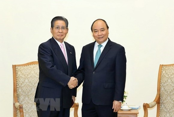Prime Minister Nguyen Xuan Phuc shakes hands with Special Advisor to the Japanese Cabinet Isao Iijima at their meeting in Hanoi on March 23. (Photo: VNA)