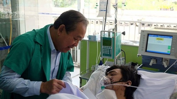 Deputy PM Binh visits a fire victim at Cho Ray Hospital (Photo: SGGP)