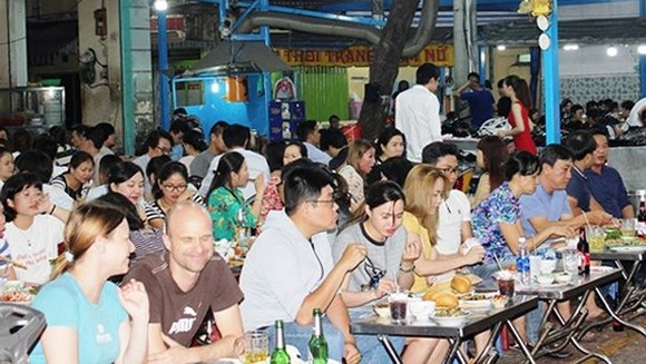 People enjoy their dishes in the new food street (Photo: SGGP)