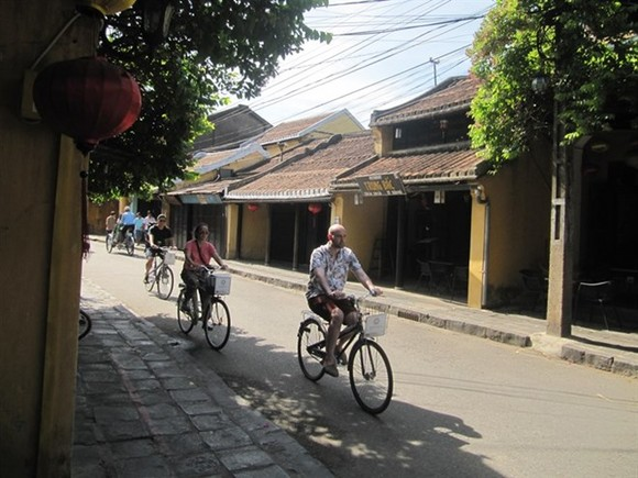 Tourists pedal in an old street of Hoi An (Photo: VNA)