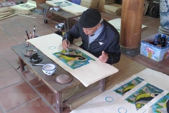 Artisan Nguyen Dang Che finishes a Dong Ho painting called Ca Chep Trong Trang (Moonlight Carp) (Photo: VNA)