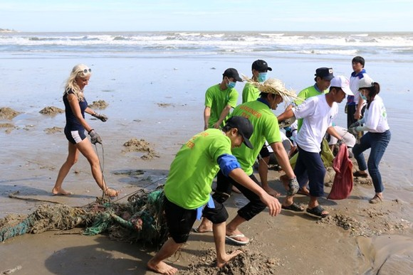 Foreigners and local people join hands to clean Mui Ne beach on July 12 (Photo: VNA)