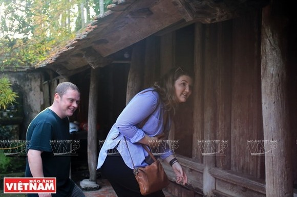 Tourists walk into a house in Duong Lam ancient village (Photo: VNA)