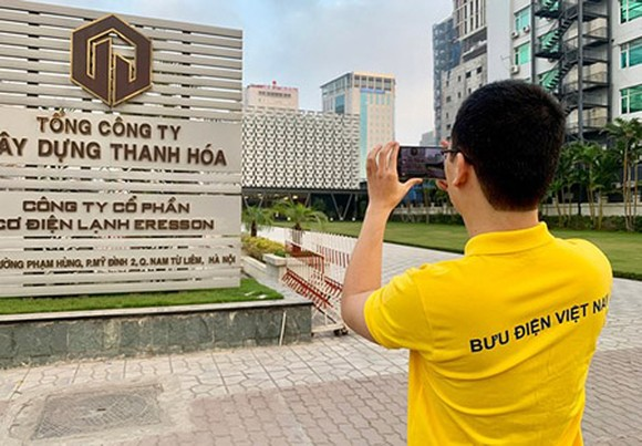 A post officer is collecting information for an address in Hanoi.