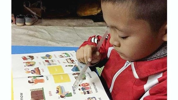 8-year-old Nguyen Thanh Dat  is reading his English book (Photo: SGGP)