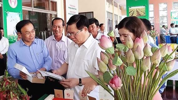 Deputy PM Vuong Dinh Hue sees produce  at the meeting (Photo: SGGP)
