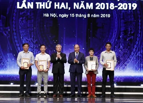 """Prime Minister Nguyen Xuan Phuc (third from right) and the winners of press awards for the fight against corruption and wastefullness.""""(Photo: VNA)"""