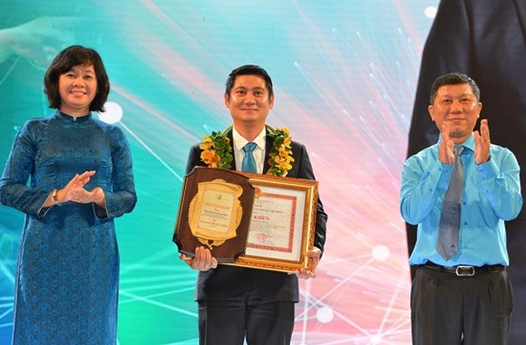 Deputy Editor-in Chief of Sai Gon Giai Phong Newspaper Ly Viet Trung gives prizes to a winner at the ceremony. (Photo: SGGP)