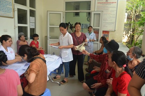 People wait for their turn for free examination (Photo: SGGP)