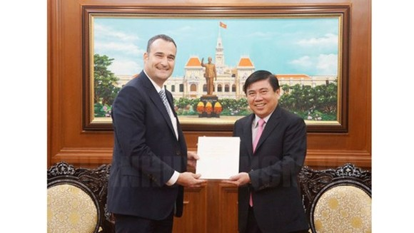 Ho Chi Minh City People's Committee Chairman Nguyen Thanh Phong offers a souvenir to new Canadian Consul General  in Ho Chi Minh City Kyle Nunas (Photo: HCMC Gov)