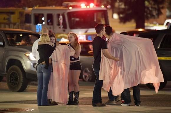 人們逃出酒吧後在街道上相互擁抱安慰。(圖源:AP)