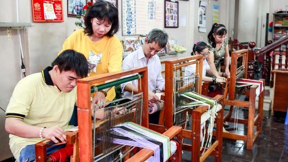 阮氏清水老師(左二)和胡氏金釵老師(右邊)在給學員們指導紡織方法。