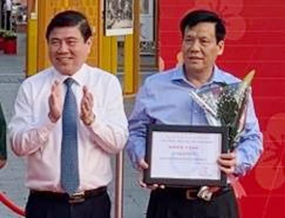 市人委會主席阮成鋒(左)向《西貢 解放報》副總編輯、華文《西貢解放日 報》主編阮玉英(紅藍)頒獎。