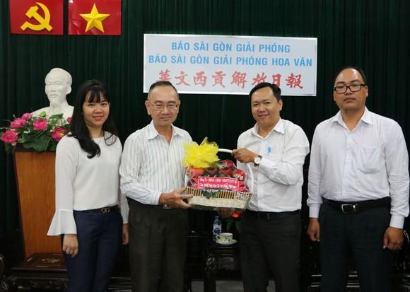 本報編輯部主任范興(左二)接受代表團的賀禮。