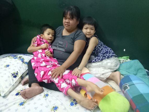 許垂玲抱著四肢癱瘓的幼女薔薇。
