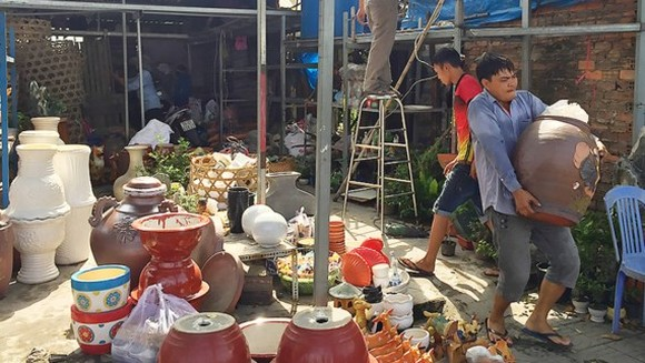 The owner of a kiosk in Truong Chinh street removes goods after authorized agencies conduct coercive removal measure (Photo: SGGP)