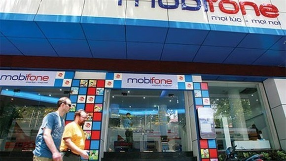 Two foreigners walk pass a customer centre of Mobifone, a State-owned enterprise (SOE) which was under equitisation process. Transparency in privatising SOEs must be enhanced to attract foreign strategic investment. (Photo: vneconomy.vn)