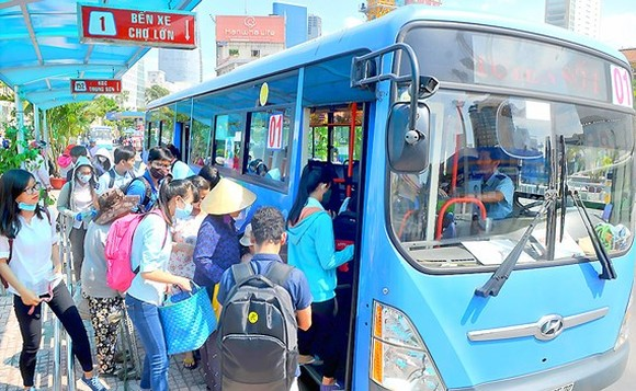 Passengers get on a bus in HCMC (Photo: SGGP)