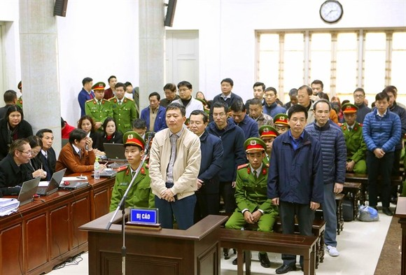 Trinh Xuan Thanh (standing in white jacket), and accomplices listen to the prosecutor's arraignment. (Photo: VNA/VNS)