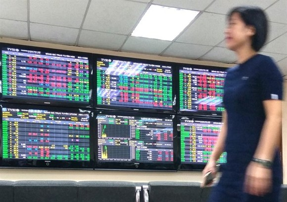An investor passes by trading screens at Tan Viet Securities Company in Hanoi. (Photo: VNA)
