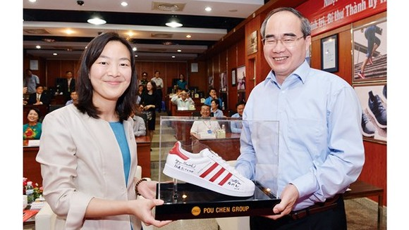 HCMC Party Chief puts his signature to shoe products of Pou Yuen Vietnam (Photo: SGGP)