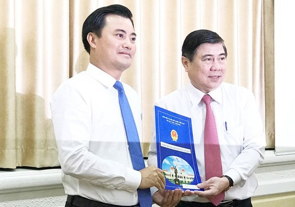 Chairman Nguyen Thanh Phong gives Mr. Bui Xuan Cuong (L) the decision to appoint him to head of Urban Railway Management Board (Photo: SGGP)