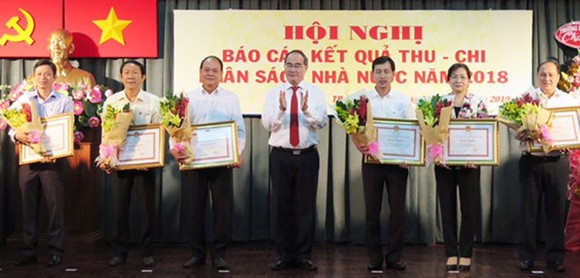 HCMC Party Chief Nguyen Thien Nhan gives certificates of merit to representatives of 24 districts for well fulfilling their budget revenue mission in 2018 on January 3 (Photo: SGGP)